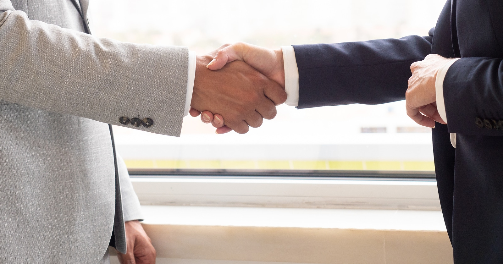 Business people shaking hands. Close-up partial view of professional businessman and businesswoman shaking hands in office. Business agreement concept